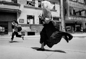 Women run across 'Sniper Alley' during heavy shooting in Sarajevo in 1995.