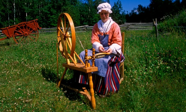 A woman in traditional costume at a spinning wheel.