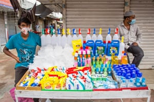 A masked man sells disinfectant and personal protective equipment on the street