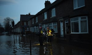 Members of the RSPCA help a woman retrieve possessions from her flooded property in Carlisle.