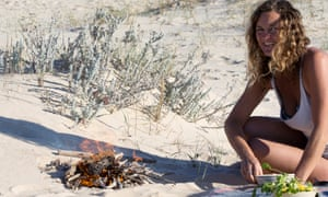 Susan Smillie crouching on a sandy beach by a small fire as she prepares lunch