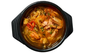 Bowl of soup with prawn and other shellfish pieces showing