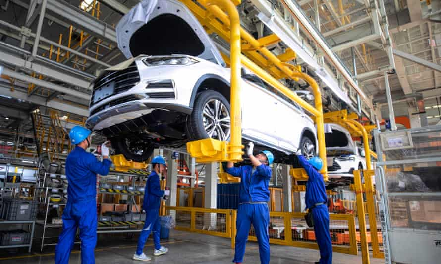 Employees work on a car at the BYD factory in Xian, China
