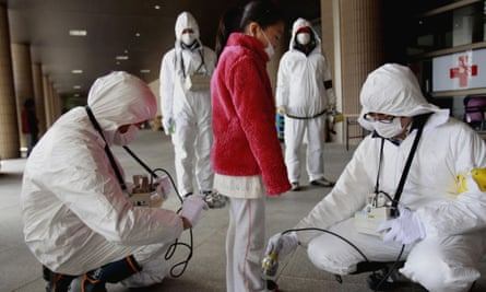 An evacuee is checked for radiation in Japan after Fukushima