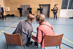 Broenderslevhallen, DenmarkInga and Erling Halmqvist wait to get their second dose of the Covid vaccine while musicians from the Aalborg Symphony Orchestra entertain them. Live music at North Jutland vaccination centres has been so successful that the region is tapping into music therapy education with the help of Aalborg University, which will experiment with various forms of music at the vaccination sites