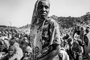 Women gather near Gwoza town waiting to be allowed to cross the trench to farm