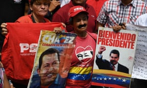 A Socialist party supporter displays placards with pictures of President Nicolás Maduro and the late leader Hugo Chávez during a May Day rally in Caracas.