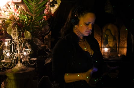Brigid Goode, a paranormal investigator, is illuminated by a green laser grid used to detect possible spirits.
