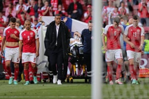 Denmark players escort Christian Eriksen as he is carried off after collapsing on the pitch during the Euro 2020 match between Denmark and Finland at the Parken Stadium