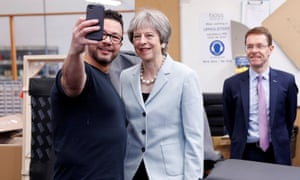 Theresa May poses for a selfie with upholsterer Derek Whitehouse as West Midlands mayor Andy Street looks on during a visit to Boss Design in Dudley