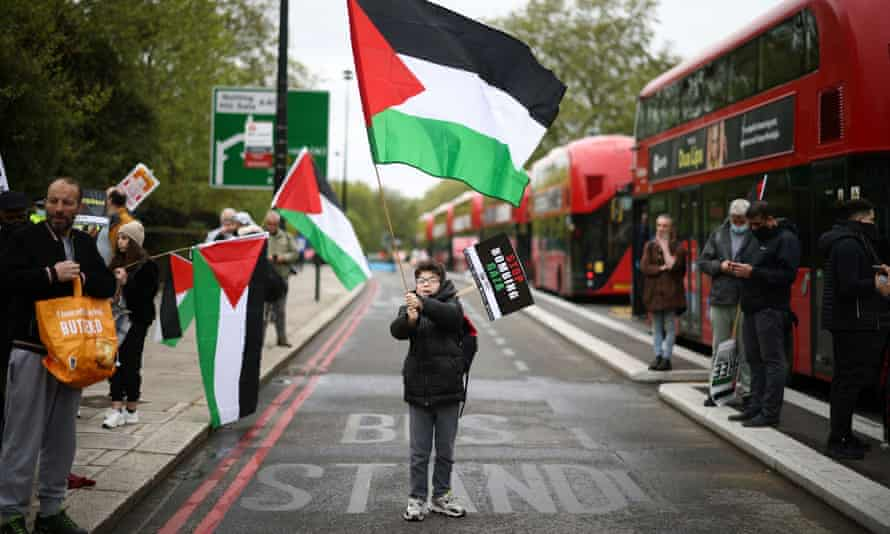 A boy waves a Palestinian flag  next to red London buses