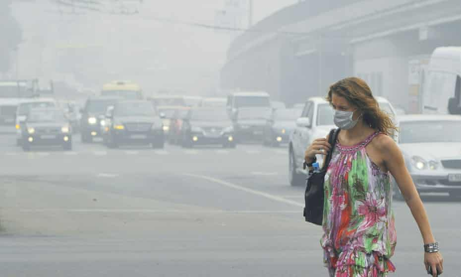 A Russian woman wears a face mask to protect herself from acrid smoke while walking in central Moscow on August 9, 2010. Air pollution from a heatwave-fueled forest fire smog caused hundreds of extra deaths each day compared to a normal period.