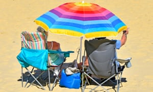 A couple under an umbrella on the beach