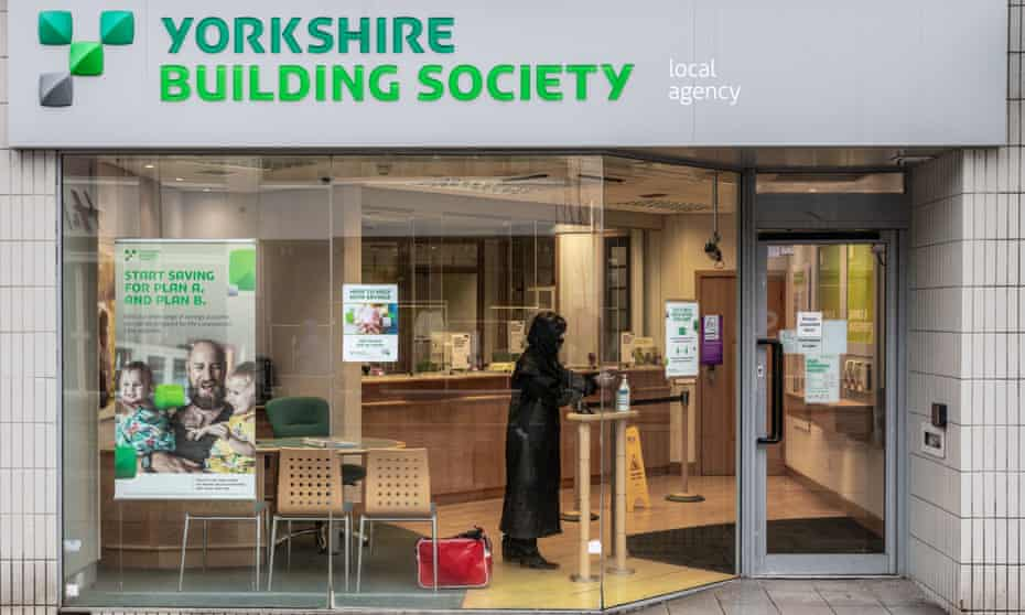 A woman sanitisers her hands inside a branch of Yorkshire building society