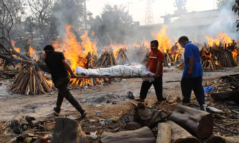 The body of a person who died from coronavirus is carried at mass cremation in New Delhi