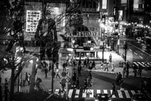 Commuters are reflected in a window in the Shibuya shopping district of Tokyo