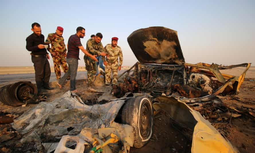 Iraqi security forces inspect the site of the bomb attack at a police checkpoint on a highway near Nasiriyah.