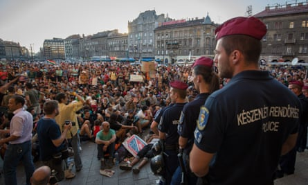 Hungarian police watch refugees gathered outside Keleti station in central Budapest last year.