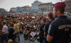 Refugees and migrants outside Keleti railway station in central Budapest, watched by police