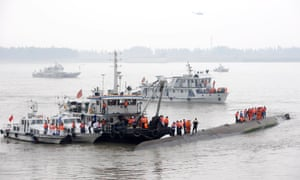 Chinese rescuers stand on the upturned bottom of the capsized cruise ship in the Yangtze River in Jianli county,