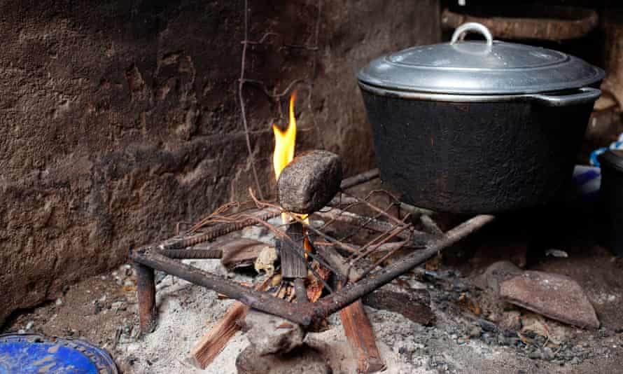 Stone used for breast-ironing is placed on a fire.