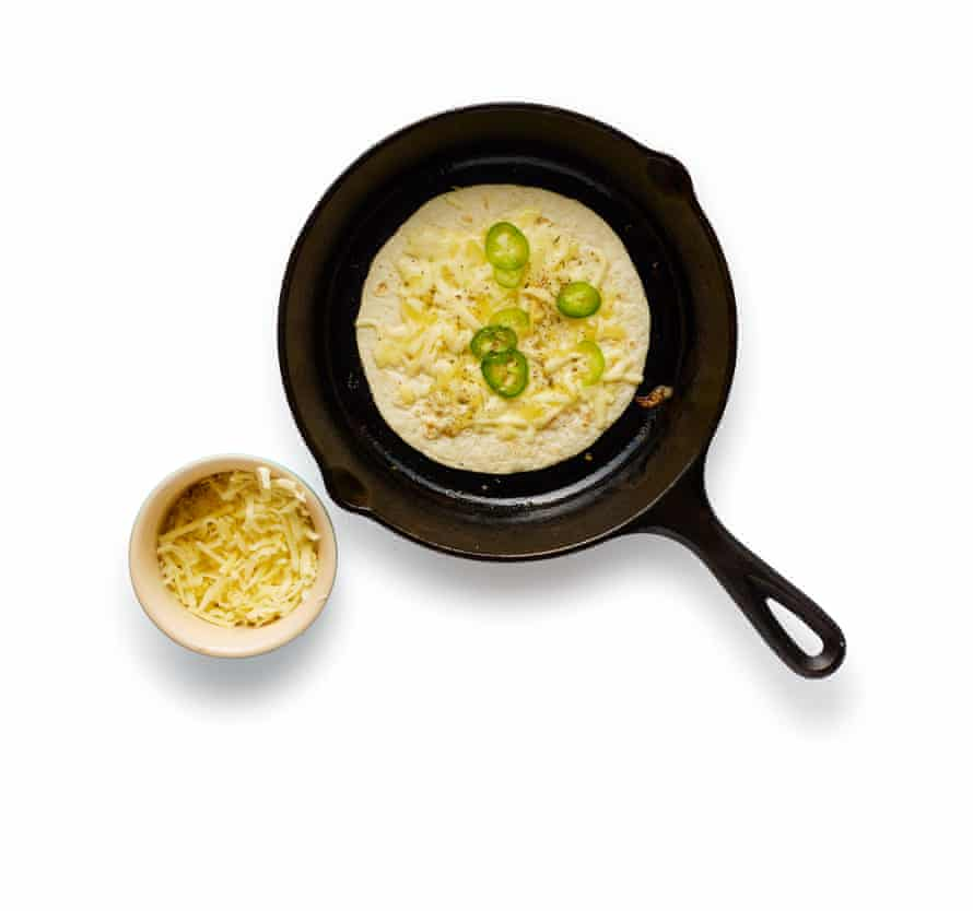 Lay a tortilla in a hot pan and top with cheese. When it starts to melt, add oregano and chilli, and keep an eye out.