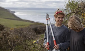 Young women with pruning shears by coast