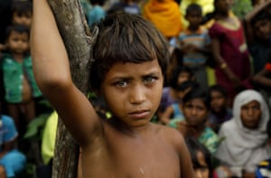 A Rohingya child stands next to newly arrived refugees who fled to Bangladesh from Myanmar.