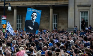 The Huddersfield Town fans hold up a banner for the chairman and owner, Dean Hoyle, as they celebrate promotion to the Premier League.