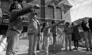 Members of Move show defiance to the police as they stand in front of their barricaded house in Philadelphia, Pennsylvania.