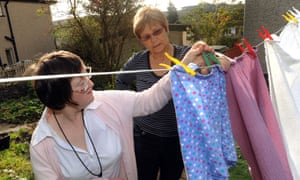 A young disabled women hangs out her washing