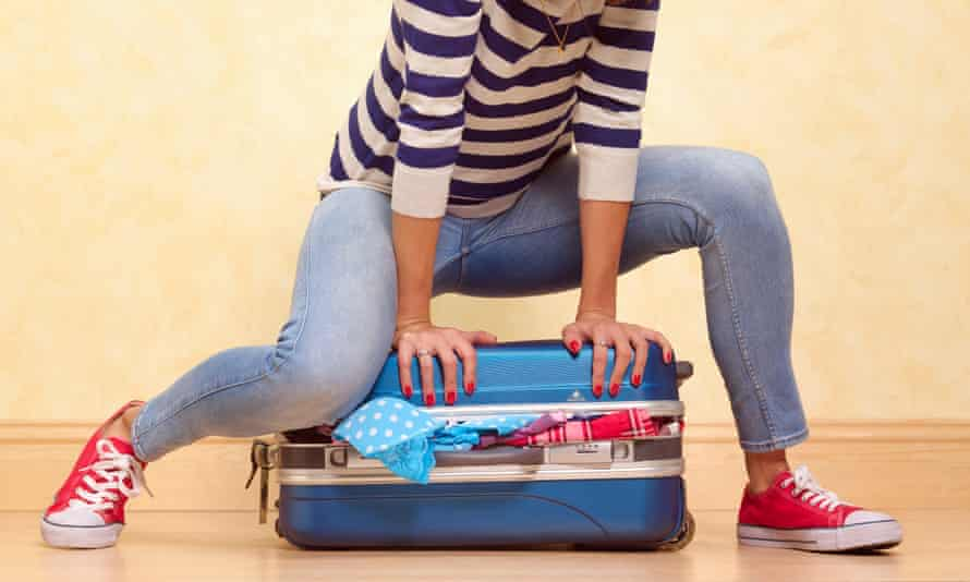 Woman pushing down lid of suitcase to try and close it