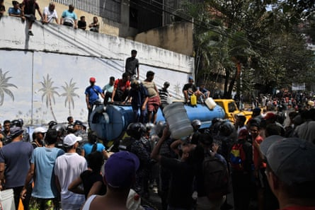 Members of the Bolivarian National Police escort a tanker as they help organize the distribution of drinking water to residents of San Agustin neighbourhood in Caracas on March 11, 2019, while a massive power outage continues affecting parts of the country.