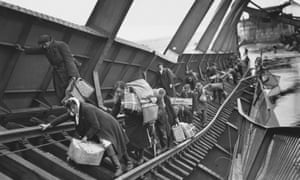 Refugees fleeing to safety behind allied lines cross a damaged railway bridge over the river Elbe in Germany on 1 May 1945.
