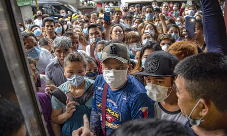 Filipinos hoping to buy face masks crowd outside a medical supply shop. Officials are trying to track those who may have come into contact with a Wuhan man who died from coronavirus in the Philippines, the first case outside China.