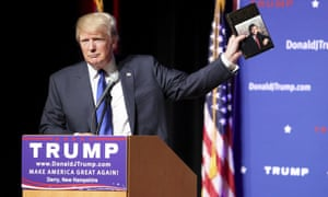 Donald Trump holds up a copy of Trump: The Art of the Deal.