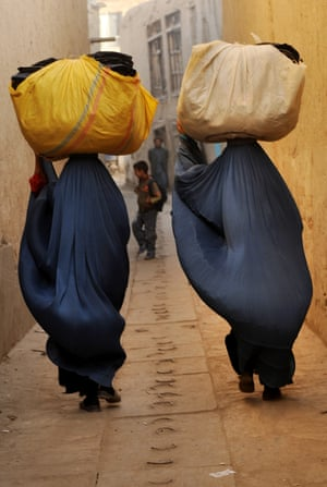 Kabul, 2009. Afghan women clad in burqas carry secondhand clothes to wash before trying to sell them.