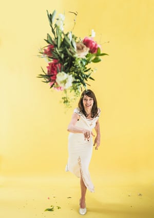 Zoe Williams in a wedding dress throwing a bouquet of flowers