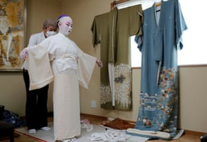 Shoichi Sanagashi, a kimono dresser, wears a protective face mask as he dresses Tokijyo Hanasaki, a jiutamai dancer, before Hanasaki is recorded dancing for a film supported by the Tokyo Metropolitan government in order to support artists during the coronavirus disease (COVID-19) outbreak, at a studio in Tokyo, Japan, June 29