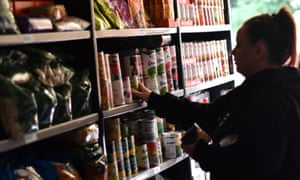 A volunteer stacks donated food on to shelves at a food bank in Stalybridge, England.