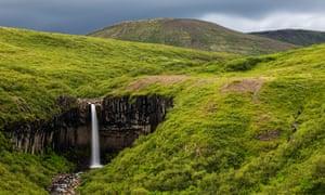 Waterfall in rolling hills in remote landscape. Svartifoss waterfall, Iceland