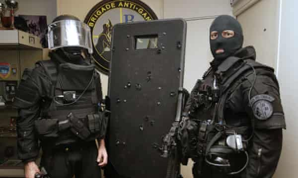 Police commandos pose with a bullet-ridden riot shield that was used during the assault at the Bataclan threatre.