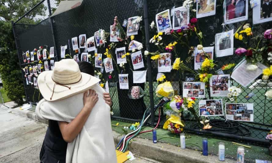 People embrace at a make-shift memorial outside St Joseph Catholic church in Surfside.