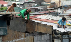 Residents along Manila Bay repair their roofs as they wait for typhoon Noul to arrive on Sunday.
