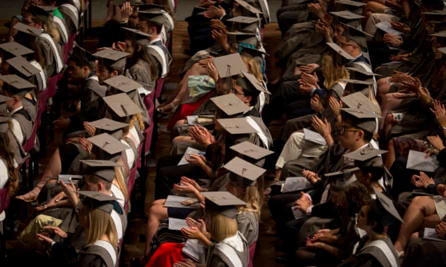 Students wearing gowns and mortarboards applaud during at their graduation ceremony.