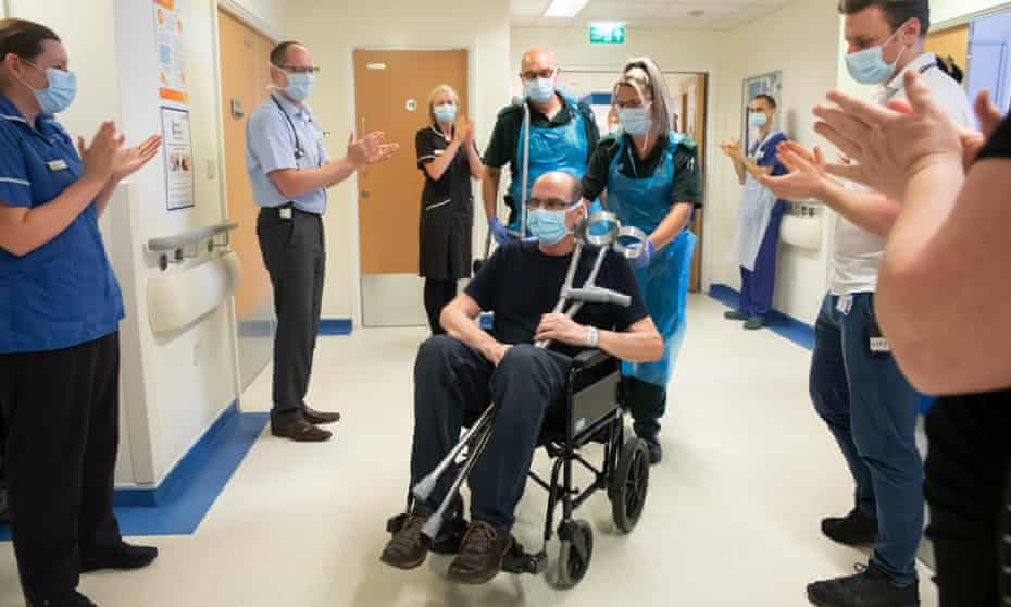 A man in a wheelchair being wheeled out of hospital past applauding staff.