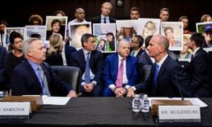 Dennis Muilenburg, right, and vice-president and chief engineer John Hamilton sit in front of people holding pictures of loved ones during a US congressional hearing.