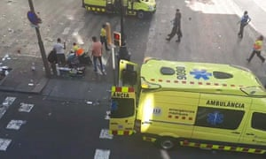 A TV image shows emergency staff and members of the public attending the injured.