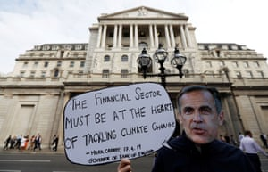 Environmental and banking system protestors demonstrate outside the Bank of England demanding that the bank rule out investment in high-carbon sectorsEnvironmental and banking system protestor wears a mask of Governor of the Bank of England, Mark Carney as they demonstrate outside the Bank of England demanding that the bank rule out investment in high-carbon sectors in London, Britain July 11, 2019. REUTERS/Peter Nicholls