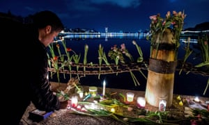 Flowers and candles placed during a vigil for those who died in a warehouse fire in Oakland.